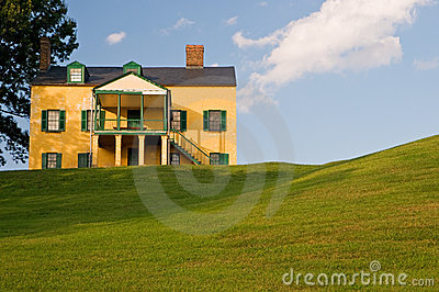 Casa amarela no monte gramíneo