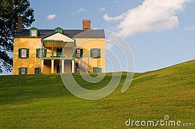 Casa amarilla en la colina herbosa