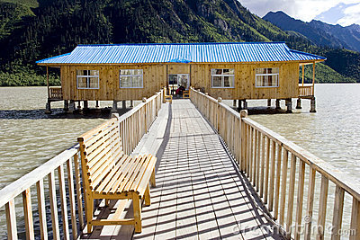 Casa de madeira no lago perto da montanha