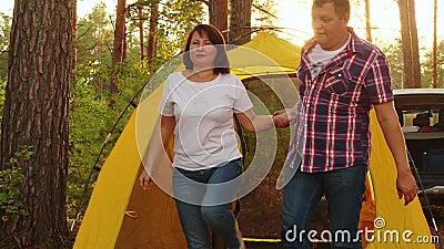 Casal de turistas acordando em tenda de acampamento na manhã ensolarada Casal feliz bocejando e esticando as mãos na tenda turíst vídeos de arquivo