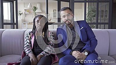 Casal multiracial bonito sentado no sofá em casa assistindo filme de terror Mulher segurando a mão do marido e com medo vídeos de arquivo