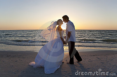 Casamento de praia de beijo do por do sol dos pares da noiva & do noivo