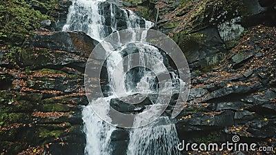 Cascada grande en la colina rocosa gris contra árboles amarillos almacen de video