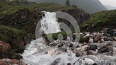 Cascada que fluye en las montañas de rocas y la hierba verde del paisaje brumoso de Islandia metrajes