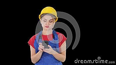 Casco d'uso del giovane appaltatore femminile professionale che manda un sms con il telefono cellulare, Alpha Channel stock footage