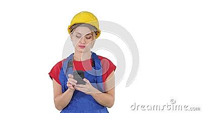 Casco d'uso del giovane appaltatore femminile professionale che manda un sms con il telefono cellulare su fondo bianco video d archivio