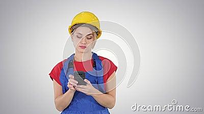 Casco d'uso del giovane appaltatore femminile professionale che manda un sms con il telefono cellulare sul fondo di pendenza stock footage