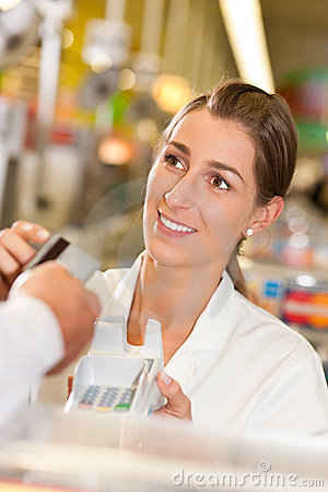 Cashier in supermarket taking credit card