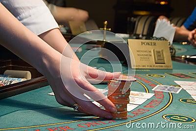 Casino dealer handling a big pile of chips