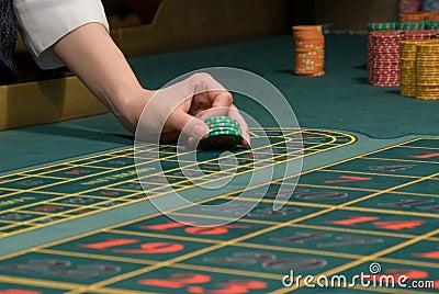 Casino dealer handling gambling chips