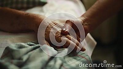 Casserole de personne âgée tenant des mains sur le lit où elle se couche banque de vidéos