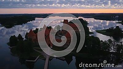 Castelo de Trakai Island, no lago Galve, Lituânia ao pôr do sol com dramáticos céus refletindo na água video estoque