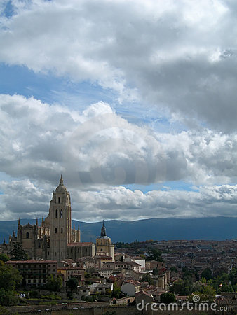 Castle on hilltop and city against cloudy sky