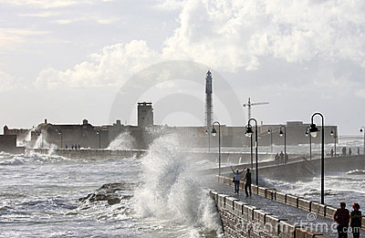 Castle and lighthouse in rough sea, Cadiz Editorial Image
