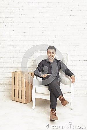 Free Casual Asian Young Man Looking At Camera While Sitting At Decora Stock Image - 65272121
