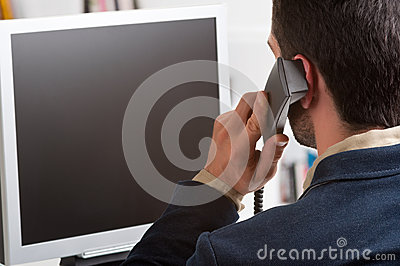 Casual Businessman Talking over the Phone and Looking at a Compu