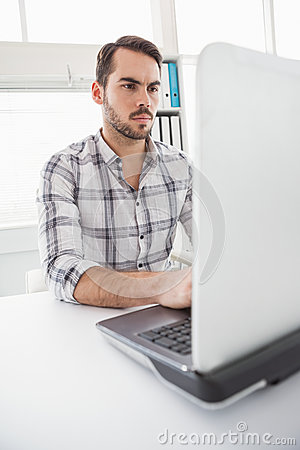 Casual businessman using his laptop at desk Stock Photo