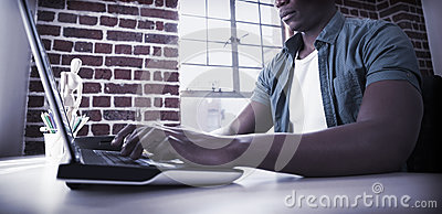 Casual businessman working on laptop at desk Stock Photo