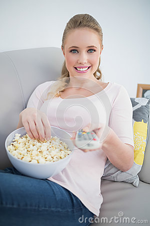 Free Casual Cheerful Blonde Holding Remote And Lying On Couch Royalty Free Stock Photos - 34401118