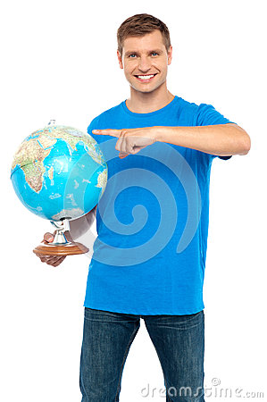 Casual cool guy pointing at rotating globe