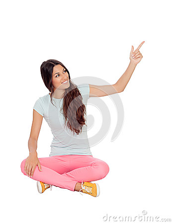 Casual girl sitting on the floor pointing something