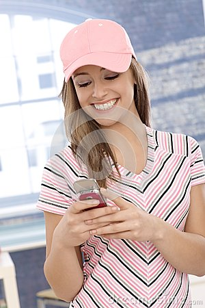 Casual girl using cellphone smiling