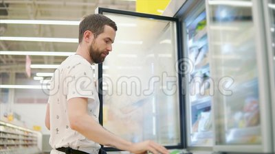 Casual guy buys food in store. Handsome man taking frozen food from shelves in a fridge of a grocery store. Man with a tattoo shopping for food, buying stock video