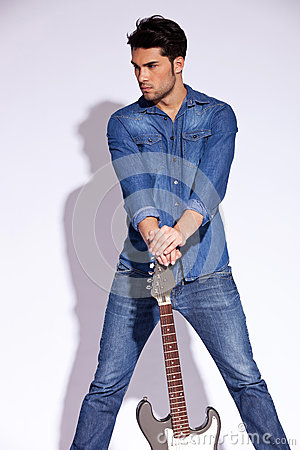 Casual man holding a guitar on the ground