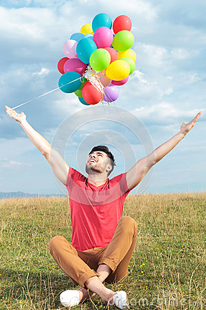 Casual man holds balloons with open arms