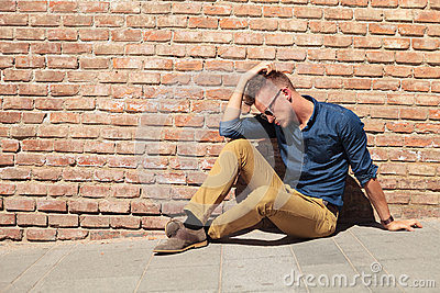 Casual man sits upset by wall
