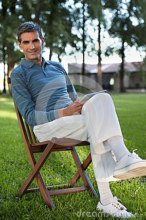 Casual Man Sitting in Park With Tablet PC