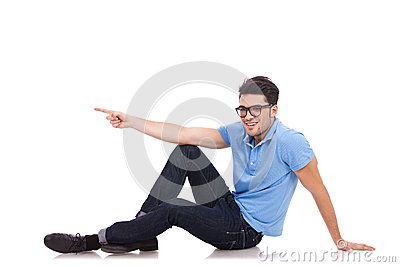 Casual man sitting pointing to a side