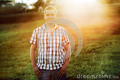 Casual man standing on the green grass in the park on the sunset
