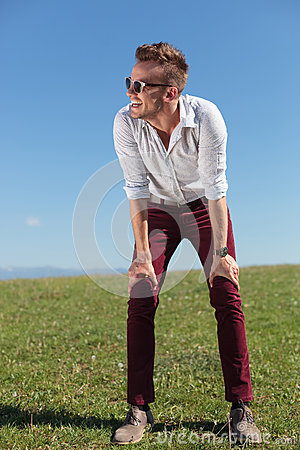Casual man stands outdoor with hands on knees