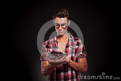 Casual man wearing glasses using a tablet