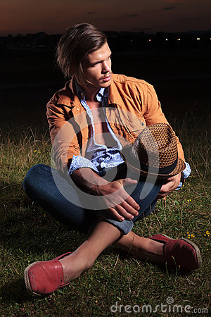 Free Casual Man With Hat On Knee Looks Away Royalty Free Stock Photos - 33658898