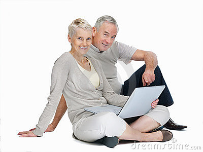 Casual old couple sitting with laptop on white