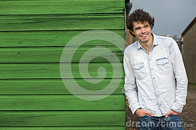 Casual Smiling Guy Leaning Against Green Wall