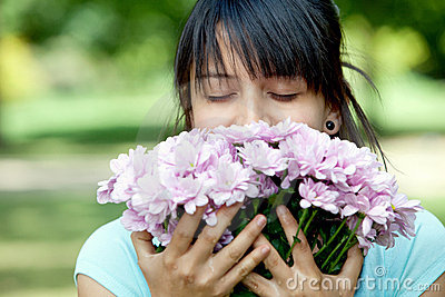 Casual woman smelling flowers