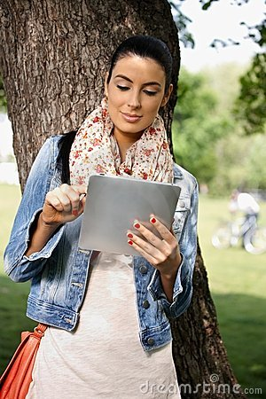 Casual woman using tablet PC outdoors
