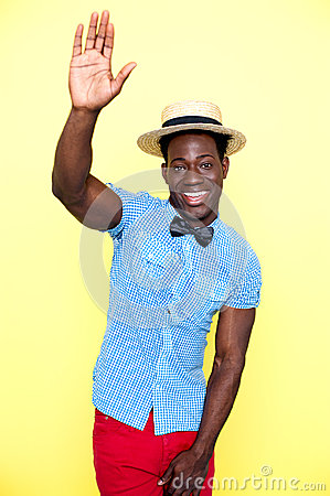 Casual young african guy posing with raised arm