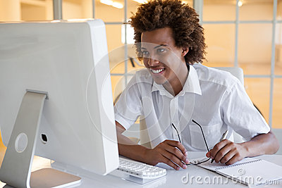 Casual young businessman sitting at his desk smiling at computer