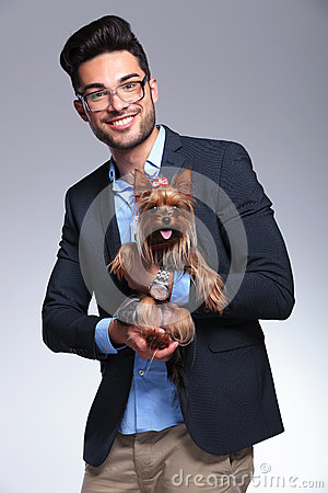 Casual young man holds puppy in both hands