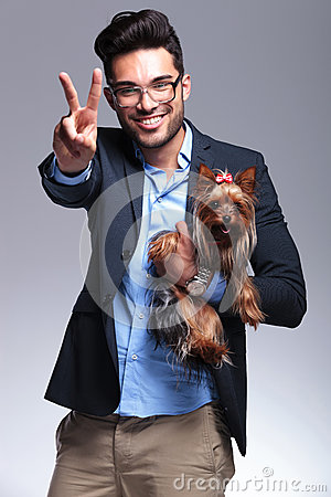 Casual young man holds puppy and shows victory