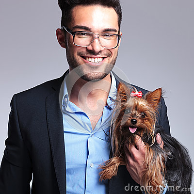 Casual young man holds puppy and smiles