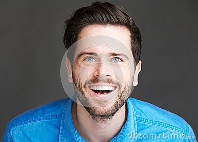 Casual young man laughing on gray background