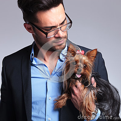 Casual young man looks at puppy