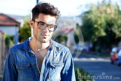 Casual young man smiling in the street