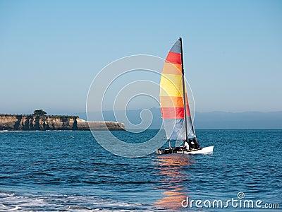 Catamaran sport sailing, red sail