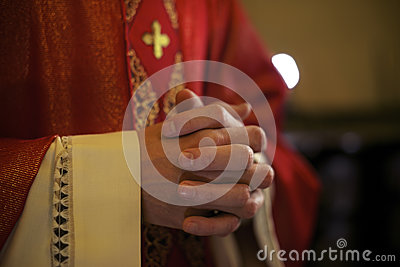 Catholic priest on altar praying during mass